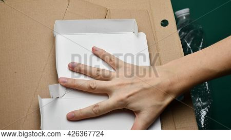 Female Hand Puts Cardboard Box At Sorting Waste For Recycling. Pov Preparation Of Recyclable Trash.