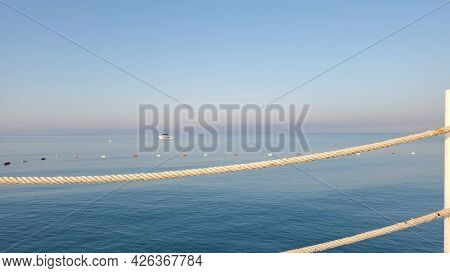 Defocused Seascape In Shades Of Pastel Colors With Morning Sunlight. Nautical Ropes On Foreground An