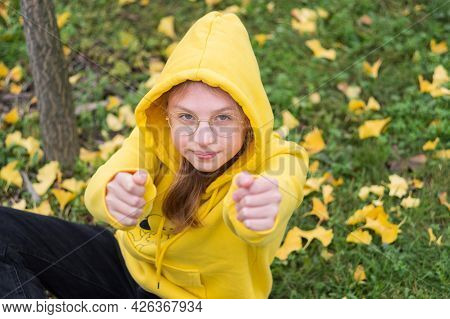 Girl Teenager In A Yellow Hoodie. The Girl Stretched Her Arms Forward. Girl In Glasses. The Girl Is