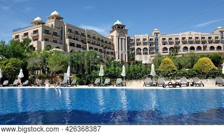 Summer Pool Resort With Arabic Style Buildings. Luxury Vacation Background With Nobody And Empty Sun