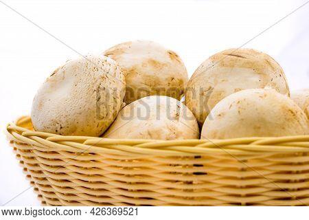 Fresh Champignons, Champignon Mushrooms In Wicker Basket Isolated