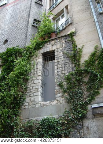 Paris, France June 2, 2007. Paris Street, Stone House With A Metal Door And Several Windows. Liana O