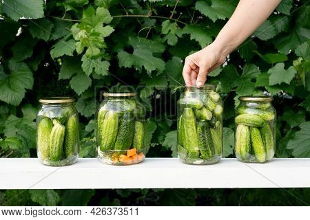 A Woman Puts Cucumbers In A Jar For Preserving Vegetables In A Marinade. Four Jars Of Cucumbers And