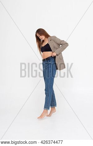 Portrait Of Young Caucasian Attractive Woman With Long Brown Hair In Blue Jeans, Black Top And Suit