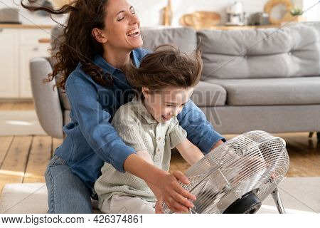 Leisure Activities For Kid At Home: Happy Mother And Small Son Enjoy Fresh Wind Blow From Metallic V