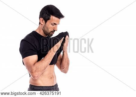 European Man, Caucasian, An Athlete, Wipes Sweat From His Forehead With A T-shirt. After A Hard Work