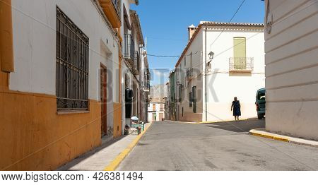 Parcent Spain - August 23 2016; Narrow Typically European Street With With Woman And Green Umbrella