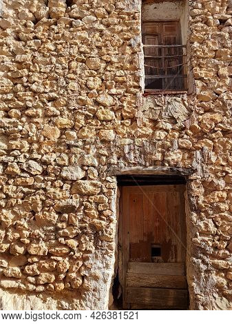 Wall Of Very Old Building Of Rocks With Two Old Doors.