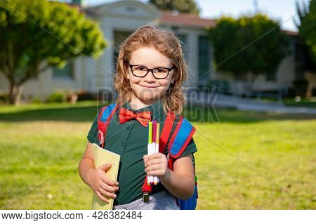 Smiling Little School Student With Backpack Book. Portrait Of Happy Schoolboy Pupil Outdoor.
