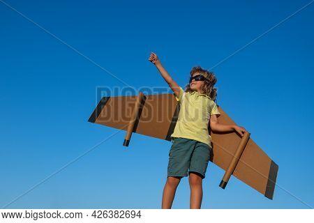 Boy Pilot Against A Blue Sky. Cute Dreamer Boy Playing With A Cardboard Airplane. Childhood. Fantasy