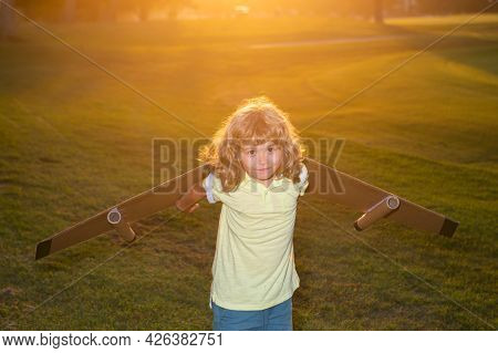 Child Playing With Toy Jetpack At Sunset Grass Field. Child Pilot Astronaut Or Spaceman Dreams Of Fl