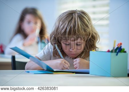Kid Studying At School. Schoolchild Doing Homework At Classroom. Education For Kids.