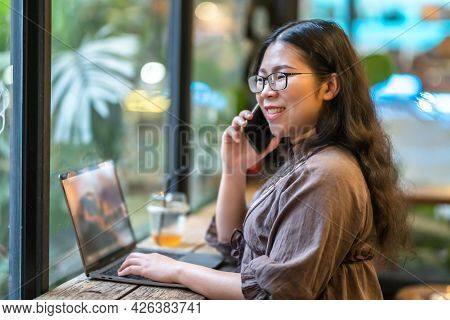 Happy Of Asian Freelance People Business Female  Hold Pick Up Smartphone Casual Working With Laptop
