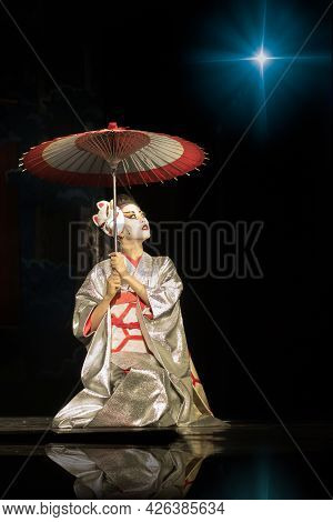 Geisha In Traditional Kimono With Umbrella Sitting On The Knees In Darkness, Lighten By The Star And