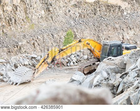 Excavator During Earthmoving Work At Open-pit Mining On Gravel Quarry Background. Loader Machine Wit