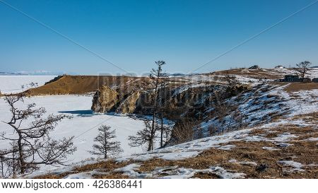 Snow Lies On The Steep Banks Of The Frozen Lake, Dry Grass And Bare Trees Are Visible. Shadows And T