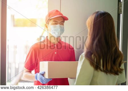 Deliver Man Wearing Face Mask In Red Uniform Handing A Parcel Box Over To A Customer In Front Of The