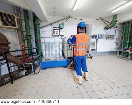Manipulator In Chemical Operation Wearing Reflective Vest, Blue Helmet And Rubber Work Boots. A Man