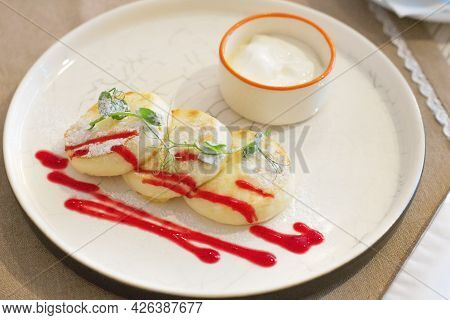 Cheesecakes With Sour Cream. Yummy Dessert. Cheesecakes On A White Plate. Traditional Russian Dish.