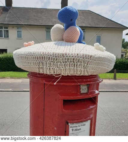 LONDON, UK - 9th July 2021: Red London Post box decorated with a woollen hat, to celibate the 100th year of the Becontree  Estate, in Dagenham, East London.