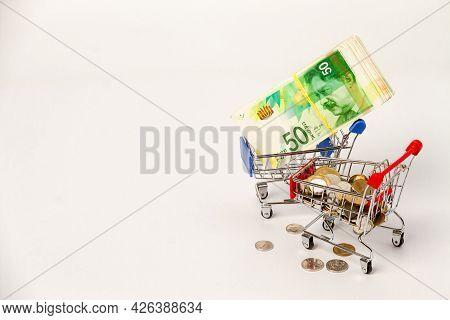 A Bundle Of 50 New Israeli Shekels Bills On A Grocery Trolley And Israeli Coins On A Grocery Trolley