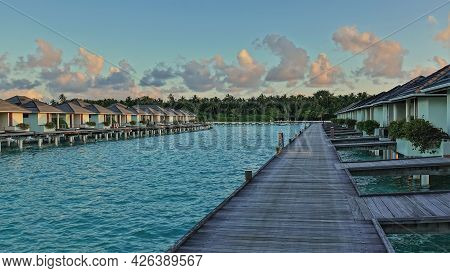 A Wooden Path Leads Over The Avquamarine Ocean To The Water Villas. In The Blue Sky, Golden Morning