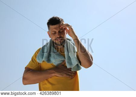 Man With Towel Suffering From Heat Stroke Outdoors