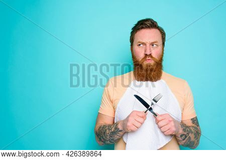 Man With Tattoos Is Ready To Eat With Cutlery In Hand With Some Doubt