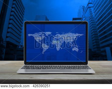 Start Up 2022 Business Icon With Global Words World Map With Modern Laptop Computer On Wooden Table