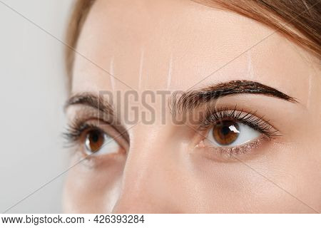 Woman During Eyebrow Tinting Procedure On Grey Background, Closeup