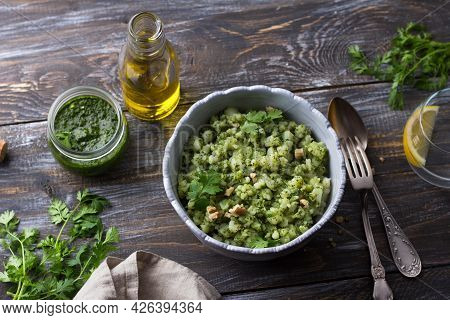 Homemade Potatoes Crumpled With Pesto Sauce, Nuts, Herbs And Olive Oil On A Wooden Table, Top View