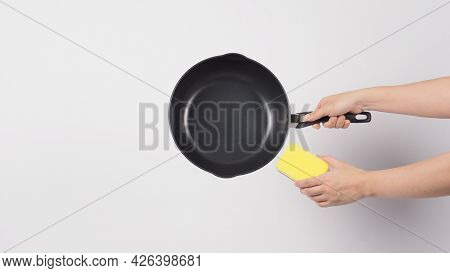Pan Cleaning. Man Hand On White Background Cleaning The Non Stick Pan