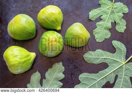 Ripe Fig Fruit And Green Leaves Of A Fig Tree On Black Metal Background.  Flat Lay