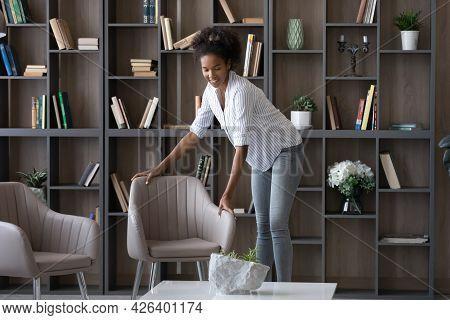 Smiling African American Woman Tenant Renter Decorating Modern Apartment