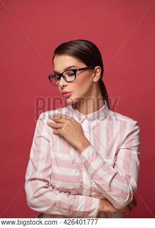 Clever Young Woman In Glasses On Red Background