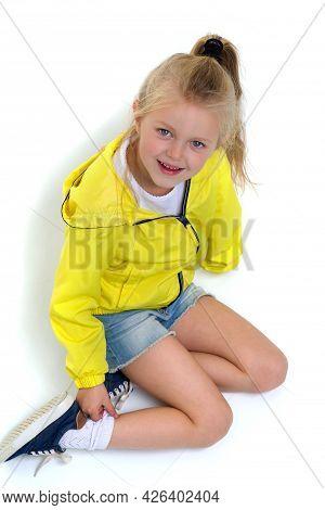 Six Years Old Girl Sitting On Floor On Her Knees. Happy Smiling Blonde Girl Posing In Studio Wearing