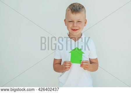 Children's Hands Holding A House Made Of Green Paper. Concept Of Ecological Houses