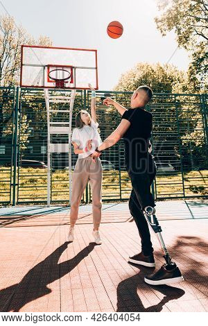 Young Man With Prosthetic Leg Playing Basketball With His Friend At A Court