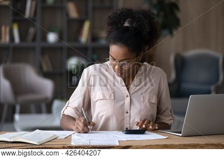 Serious African American Woman In Glasses Calculating Expenses, Using Calculator