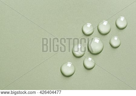 Cosmetic Moisturizing Gel Drops On Green Background, Copy Space. Transparent Liquid Skin Care Drops.