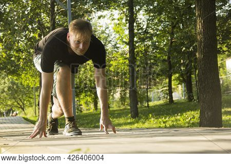 A Young Man Is Preparing For A Run. The Man Is Preparing To Run From A Low Start. Jogging In The Par