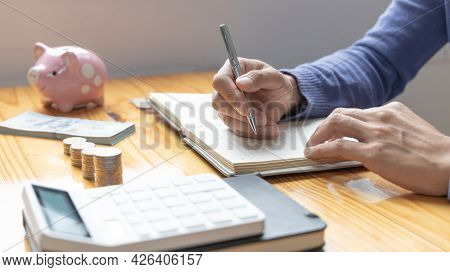 Men Are Taking Notes On Household Income And Expenses And Working To Save Money For Future Use, Mone