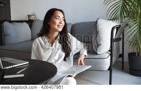 Resting Asian Woman Reading Magazine At Home, Sitting In Living Room On Relaxing Weekend And Looking