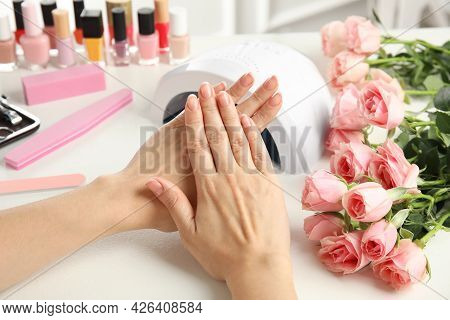 Woman Doing Manicure With Ultraviolet Nail Lamp At White Table, Closeup