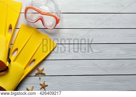 Goggles, Flippers And Starfishes On Light Wooden Background, Flat Lay With Space For Text. Beach Obj