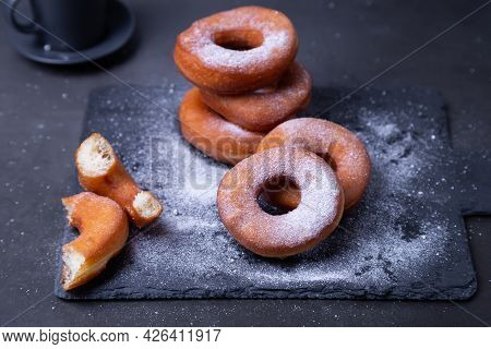 Donuts With Powdered Sugar And A Cup Of Coffee. Traditional Donuts In The Shape Of A Ring Fried In O