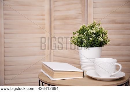 Close Up Of Cup, Plant And Book On The Table With Copy Space Over Wooden Background