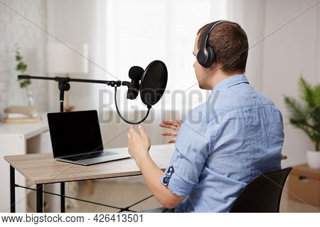 Podcast And Blogging Concept - Back View Of Male Host Or Blogger Recording Audio Podcast In Home Stu