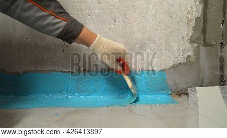 Close-up Of A Hand Applying Waterproofing In The Bathroom. The Process Of Applying Waterproofing Mor