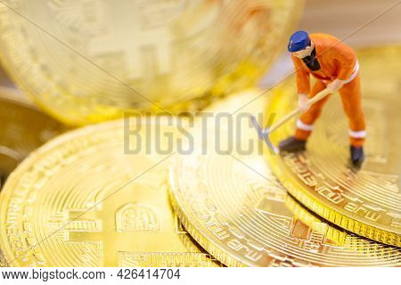 Miniature People Miner Figure Working On Gold Bitcoin.  Concept Of Business, Money, Technology, Cryp